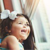 niña sonriendo con su madre a través de una ventana